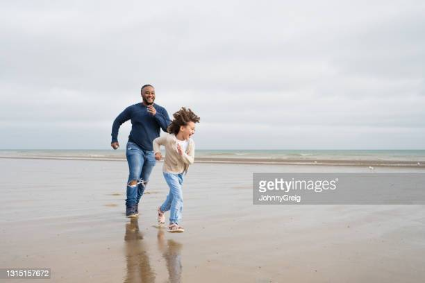 british father and young daughter playing at camber sands - moving after stock pictures, royalty-free photos & images