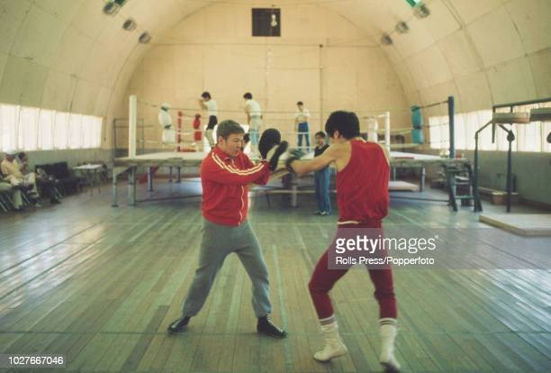 British featherweight boxer Terence Spinks pictured on left coaching a member of the South Korean boxing team in a gym prior to competition at the...