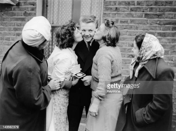 British featherweight champion boxer Terry Spinks is congratulated by his neighbours in Morgan Street Canning Town London after he a won gold medal...