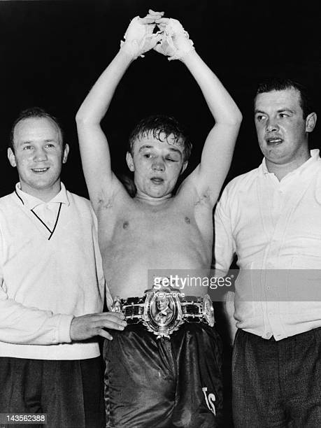 British featherweight champion boxer Terry Spinks shows off his belt after retaining his title by a knockout in a match against Bobby Neill at...