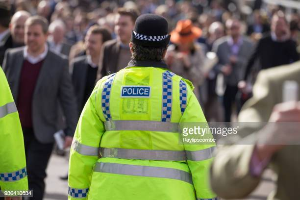 british female police officer mingling with crowds of people on their way to the famous cheltenham festival in the cotswolds. - police taser stock pictures, royalty-free photos & images