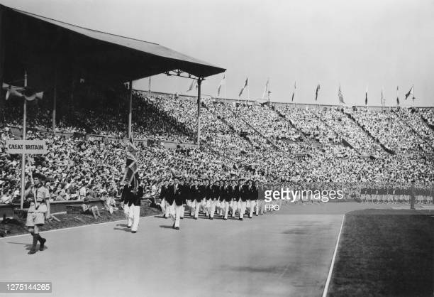 British fencer John Emrys Lloyd carrying the Union Jack as he leads the Great Britain Olympic team in the opening ceremony of the 1948 Summer...