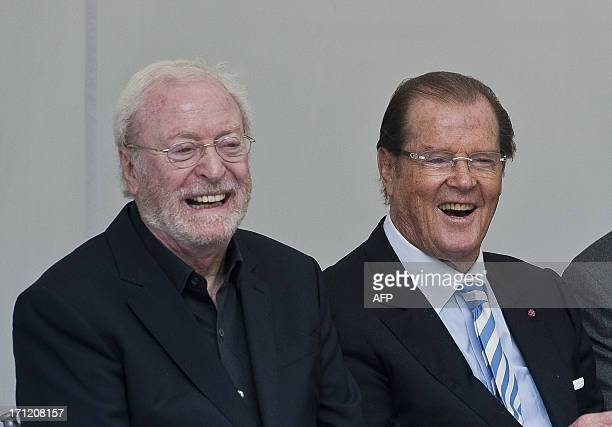 British film actors Michael Caine and Roger Moore laugh during a memorial to the late film director and restaurant critic Michael Winner at the...