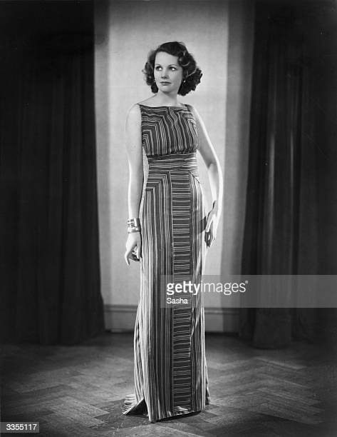 British film actress Elizabeth Allan wearing a long striped dress