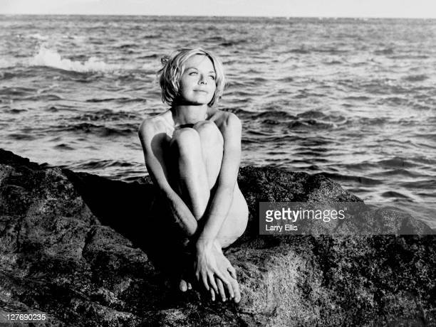 British film actress Susannah York poses seminaked on a rocky coastline during the filming of 'Duffy' a Columbia caper film 1967