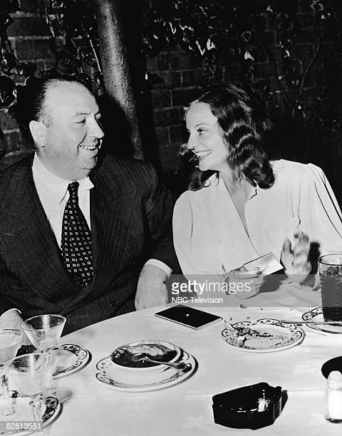 British film director Alfred Hitchcock sits at a restaurant table with American actress Tallulah Bankhead who smiles and taps her cigarette case...