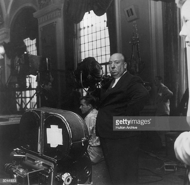 British film director Alfred Hitchcock stands next to a movie camera on the set of his film 'I Confess'
