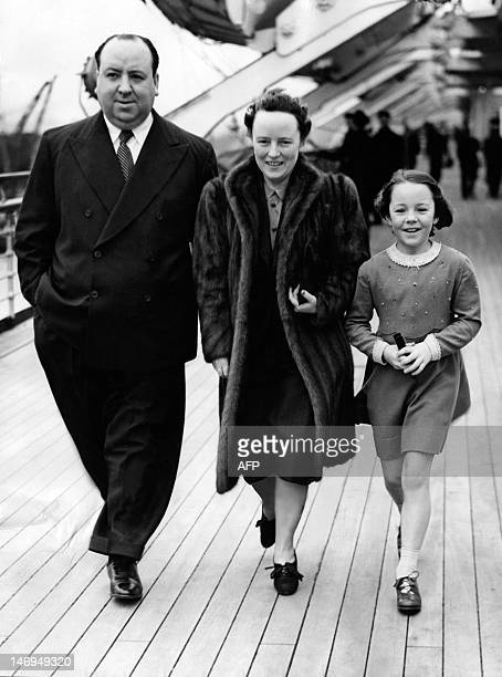 British film director Alfred Hitchcock walks with his wife Alma Reville and their daughter Pat Hitchcock aboard the Queen Mary at Southampton Great...