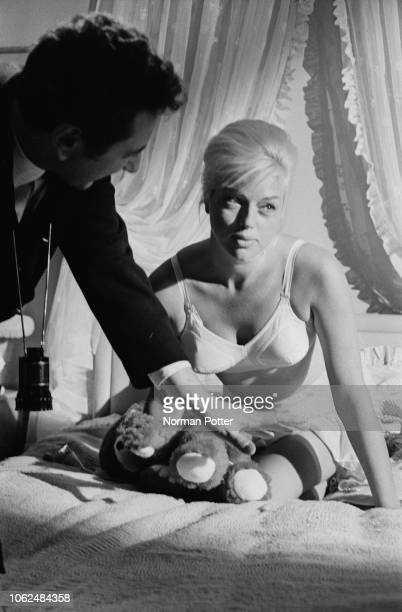 British film director and producer Michael Winner filming English actress and singer Diana Dors posing on a bed with a teddy bear as 'Georgia' on the...