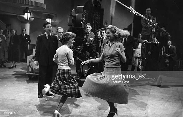 British film director Charles Crichton instructs actresses Petula Clark and Diana Dors during a boogie woogie scene from the Rank/Ealing film 'Dance...