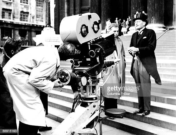British film director David Lean bends down to look through a camera viewfinder as he and his crew prepare to film a scene from his epic 'Lawrence of...