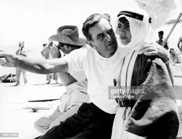 British film director David Lean explains a scene to a young actor in Arab dress on the set of his film 'Lawrence of Arabia,' 1962.