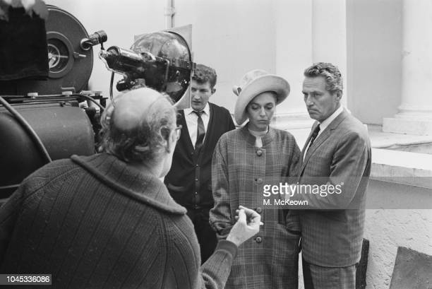 British film director Jack Clayton pictured behind the camera as he directs actors Peter Finch and Anne Bancroft on location shooting a scene from...