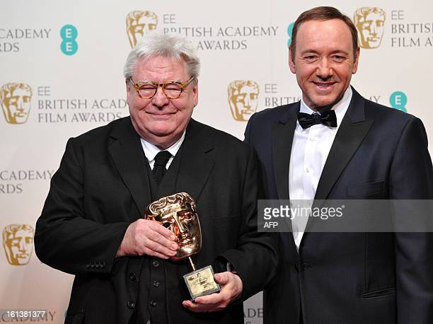 British film director producer and writer Alan Parker poses with his BAFTA fellowship award with US actor Kevin Spacey during the annual BAFTA...