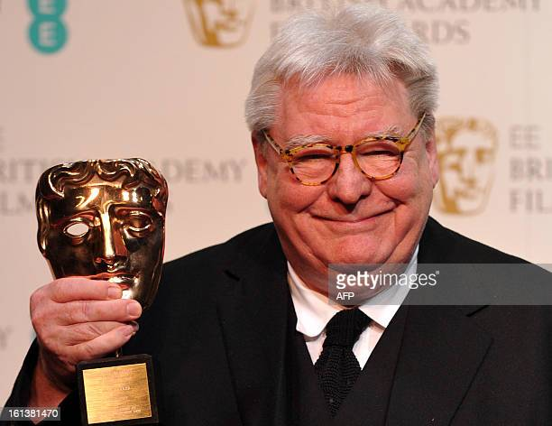 British film director producer and writer Alan Parker poses with his BAFTA fellowship award during the annual BAFTA British Academy Film Awards at...