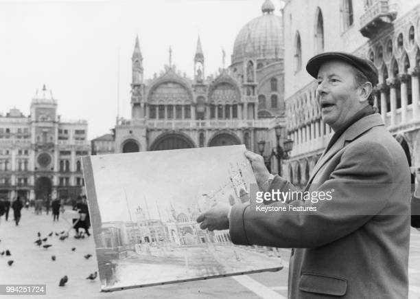 British film director Terence Young holding the painting of the Piazza San Marco in Venice painted by Catherine Deneuve's character Maria Vetsera in...