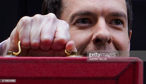 British Finance Minister George Osborne poses for pictures with the Budget Box as he leaves 11 Downing Street in London on March 16 before presenting...