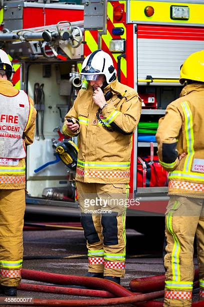 british firemen communicating at blaze scene - fire protection suit stock photos and pictures