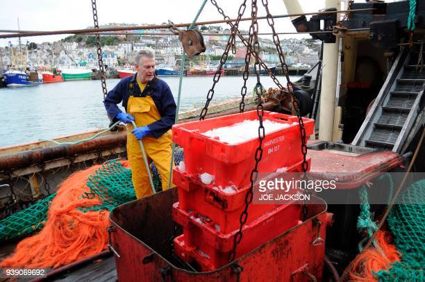 British fisherman Barry Stockton hauls crates of freshly caught fish aboard fishing trawler 'Stephanie' docked in the harbour in the fishing town of...