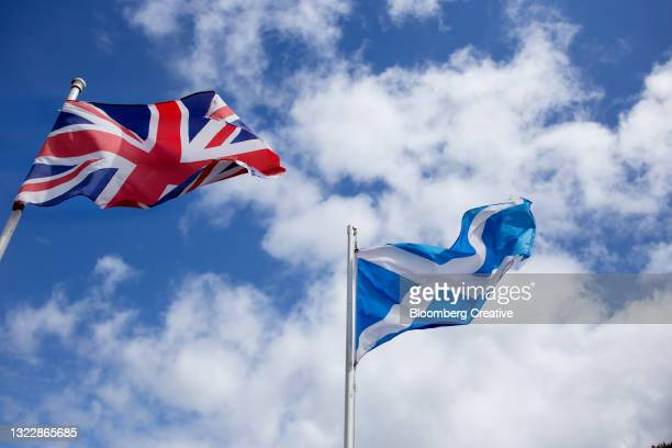 a british flag and scottish flag against a blue sky - referendum stock pictures, royalty-free photos & images