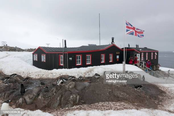 British flag flies over Port Lockroy visitors nesting gentoo penguins Goudier Island Antarctica