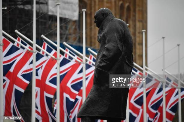 British flags seen behind the Winston Churchill statue outside of the Houses of Parliament on January 30, 2020 in London, United Kingdom. At 11.00pm...