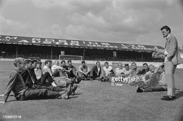 British football manager and former footballer Jimmy Hill talking to the Coventry City players who are sitting on the pitch at the club's Highfield...