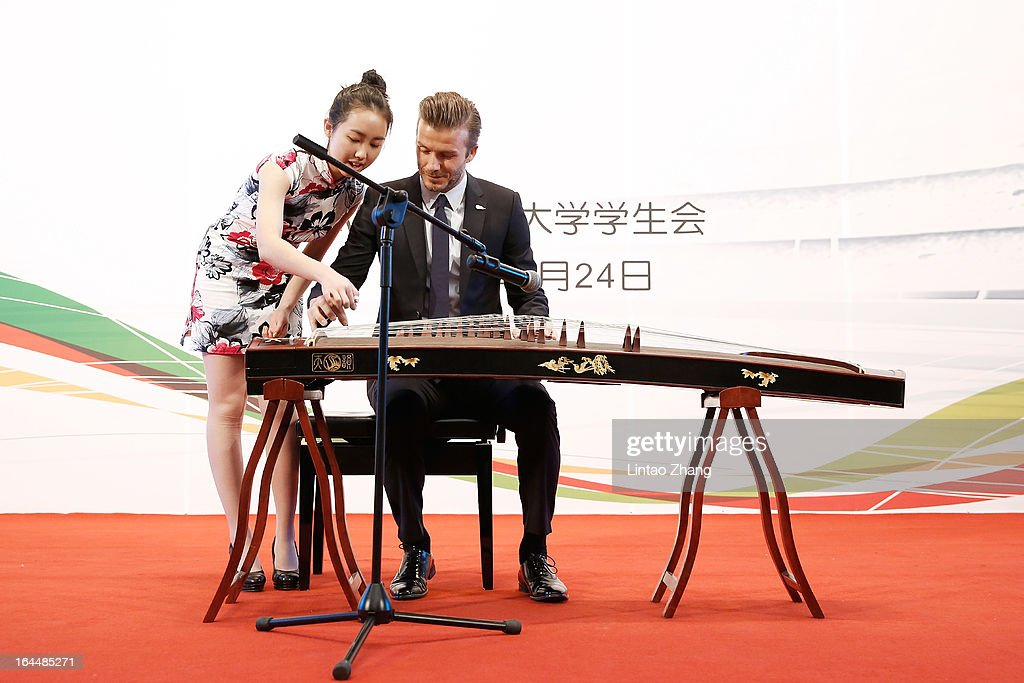 British football player David Beckham learns to play Chinese musical instruments during visit to Peking University on March 24, 2013 in Beijing, China. David Beckham is on a five-day visit to China at the invitation of the China Football Association as China's first international ambassador.