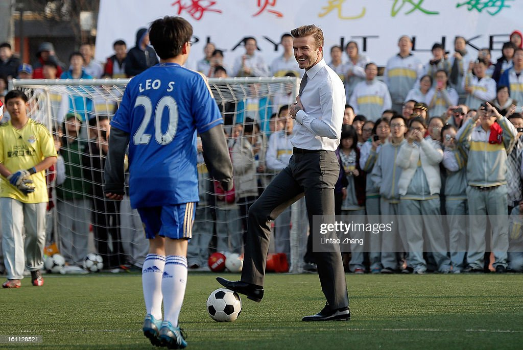 British football player David Beckham (R) plays football with students during his visit to a middle school in Beijing on March 20, 2013 in Beijing, China. David Beckham is on a five-day visit to China at the invitation of the China Football Association as China's first international ambassador.