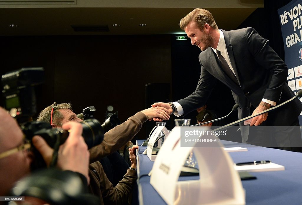 British football player David Beckham (R) shakes hands with a journalist as he arrives to give a press conference on January 31, 2013 at the Parc des Princes stadium in Paris. Beckham signed a five-month deal with the Ligue 1 leader until the end of June.