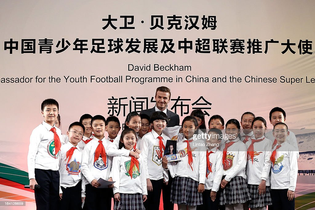 British football player David Beckham (Center) with student pose for a photo during a press conference titled 'Ambassador for the Youth Football Programme in China and the Chinese Super League' at Shijia Hutong Primary School on March 20, 2013 in Beijing, China. David Beckham is on a five-day visit to China at the invitation of the China Football Association as China's first international ambassador.