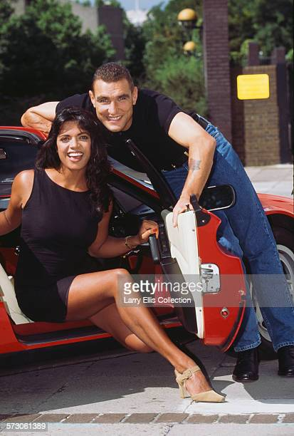 British footballer and actor Vinnie Jones poses with television presenter Jenny Powell and a red Ferrari in a promotional portrait for the launch of...