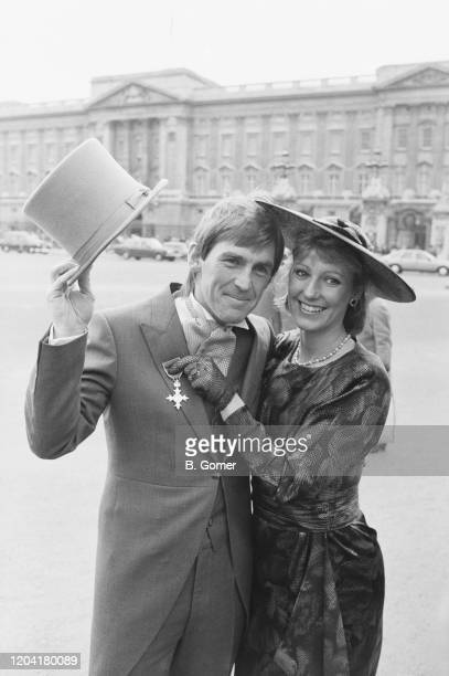 British footballer Kenny Dalglish tips his top hat as his wife, Marina, holds his MBE to his lapel at Buckingham Palace in London, England, 20th...