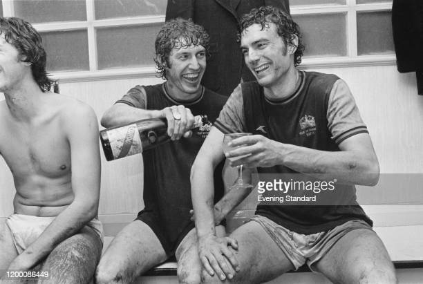 British footballer Pat Holland pouring a glass of champagne for teammate British footballer Trevor Brooking after West Ham reach the final of the...
