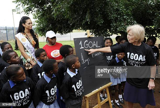 British Foreign Office Minister for Africa Baroness Glenys Kinnock and Miss South Africa 2008 Tatum Keshwar pose with pupils of Winnie Ngwekasi...
