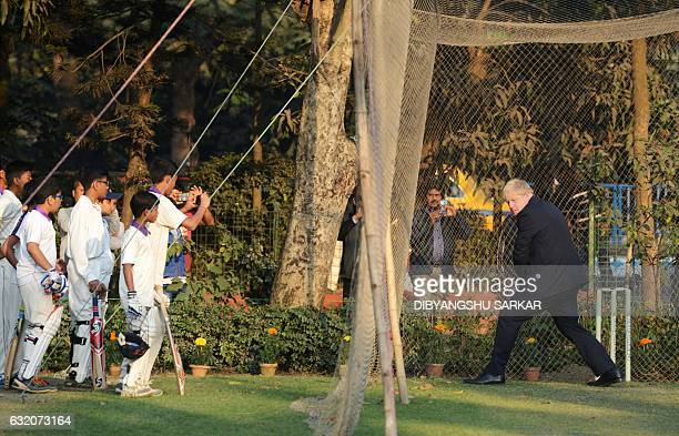 British Foreign Secretary Boris Johnson bats in the nets as cricket students look on on during his visit to the Arun Lal Cricket Academy in Kolkata...