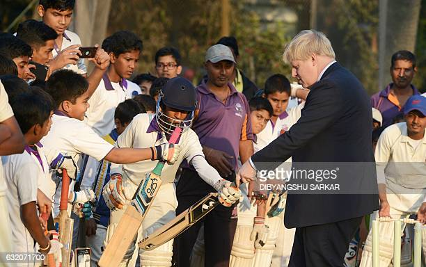 British Foreign Secretary Boris Johnson gestures as he talks with cricket students on his visit to the Arun Lal Cricket Academy in Kolkata on January...