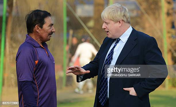 British Foreign Secretary Boris Johnson gestures as he talks with former Indian cricketer Arun Lal on his visit at the Arun Lal Cricket Academy in...