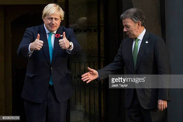 British Foreign Secretary Boris Johnson gives a thumbs up as Colombian President Juan Manuel Santos attempts to shake his hand as they visit the...