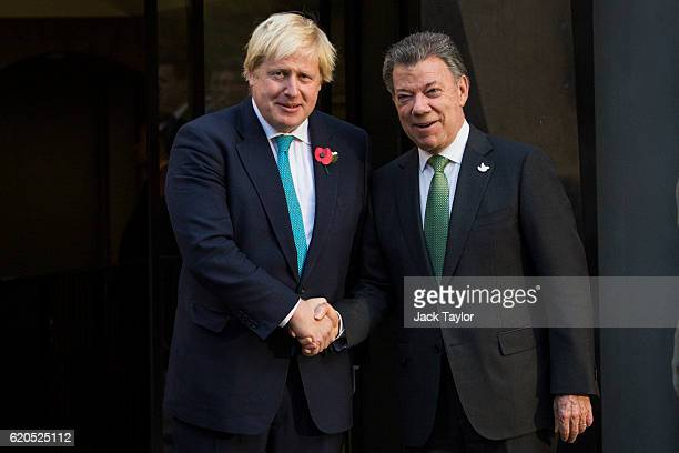 British Foreign Secretary Boris Johnson shakes hands with Colombian President Juan Manuel Santos as they visit the Churchill War Rooms on November 2,...