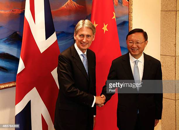 British Foreign Secretary Philip Hammond and Chinese State Councilor Yang Jiechi shake hands and face the media during the China-UK Strategic...