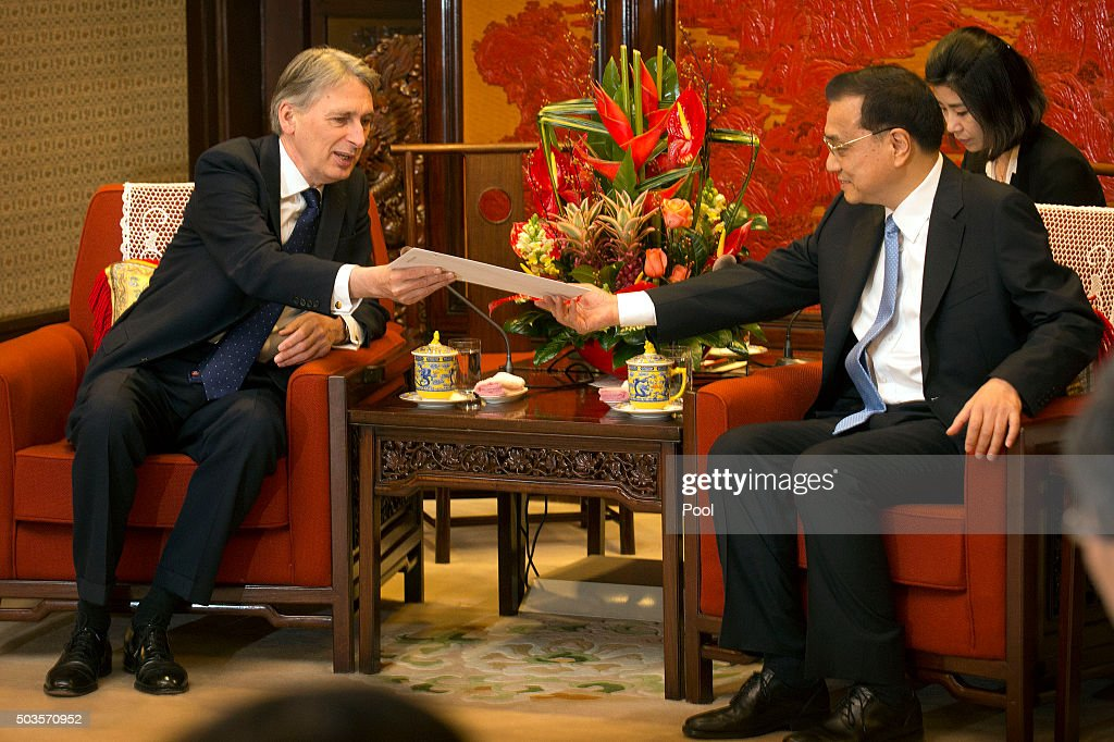 British Foreign Secretary Philip Hammond (L) hands an envelope with a letter from British Prime Minister David Cameron to Chinese Premier Li Keqiang (R) during a meeting at the Zhongnanhai Leadership Compoundon January 6, 2016 at the Diaoyutai State Guesthouse in Beijing, China.