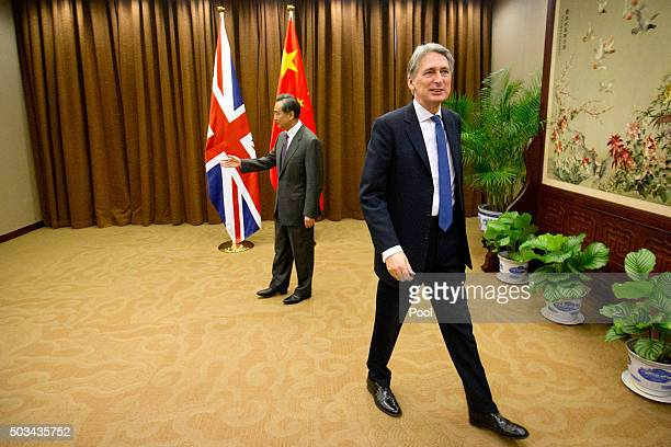 British Foreign Secretary Philip Hammond right walks away after shaking hands with Chinese Foreign Minister Wang Yi left as he arrives for a meeting...