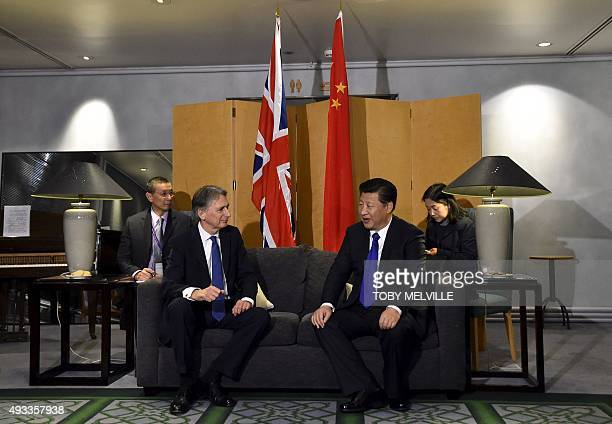 British Foreign Secretary Philip Hammond talks with Chinese President Xi Jinping following his arrival at Heathrow Airport in west London on October...