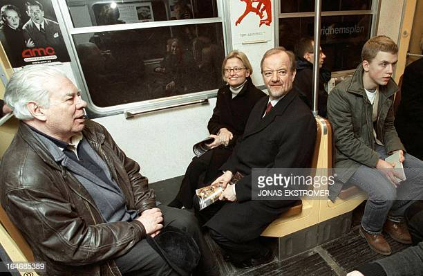 British Foreign Secretary Robin Cook sits beside Swedish Foreign Minister Anna Lindh in a Stockholm underground train 12 February 2001 on their way...