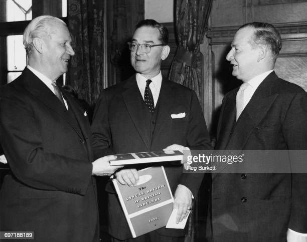 British Foreign Secretary Selwyn Lloyd presents copies of 'The Annual review of British Industry 1958' to the US and Canadian ambassadors in the...