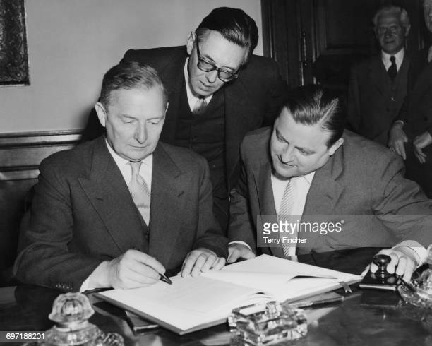 British Foreign Secretary Selwyn Lloyd signs an AngloGerman Agreement on nuclear energy at the Foreign Office in London 31st July 1956 Looking on are...