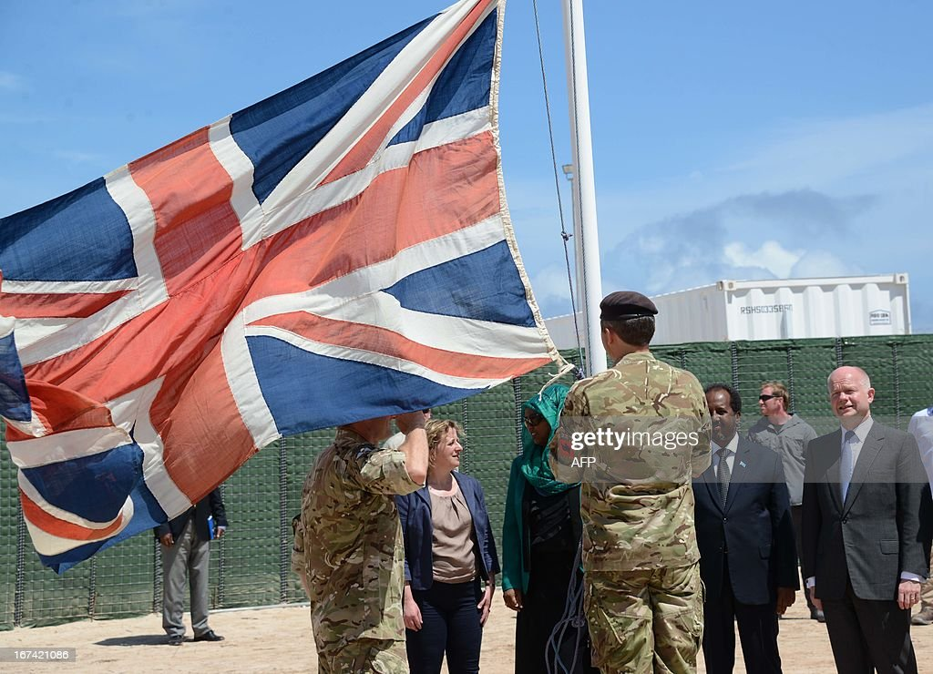 British Foreign Secretary William Hague (R) stands with Somali President Hassan Sheik Mohamud (2nd R) as a British flag is raised in Mogadishu on April 25, 2013. British Foreign Secretary William Hague opened a new embassy in Mogadishu on April 25, 22 years after London pulled its diplomats from conflict-torn Somalia. AFP PHOTO / Mohamed Abdiwahab