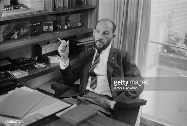 British former Formula One racing driver Stirling Moss pictured smoking a cigarette whilst seated in his Mayfair office in London on 2nd May 1963