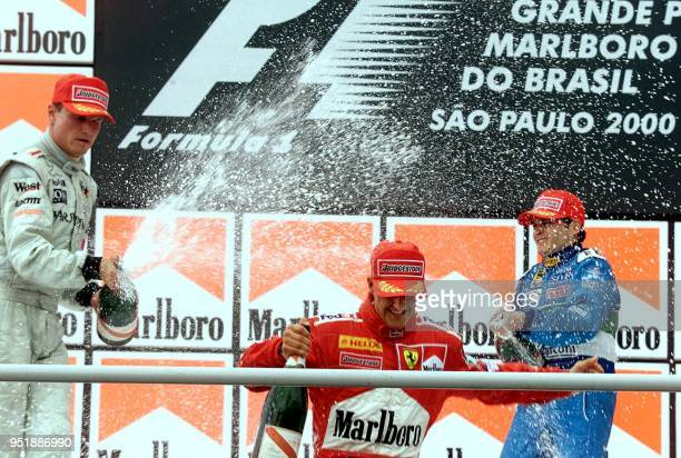 British Formula One driver David Coulthard of McLaren Mercedes and Italian Giancarlo Fisichella of Benetton sprays champagne over German Michael...
